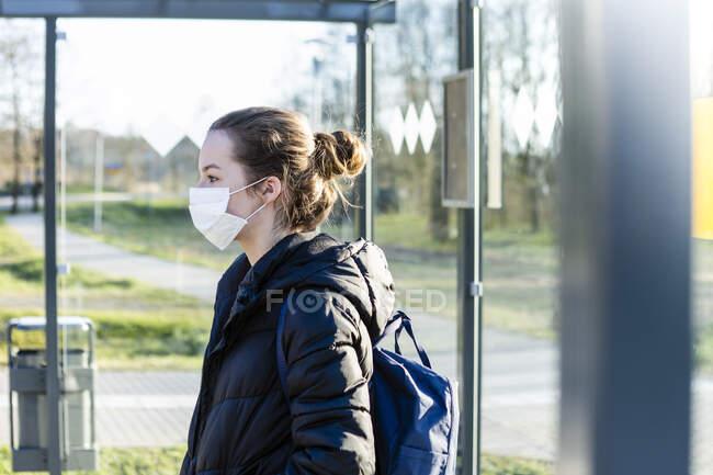 Retrato de uma menina com máscara esperando na parada de ônibus — Fotografia de Stock