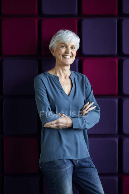 Portrait of smiling senior woman with arms crossed — Stock Photo