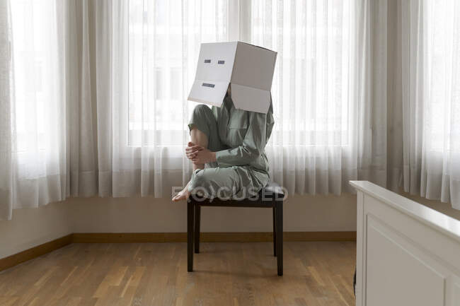Mujer con una caja de cartón en la cabeza con sonrisa aburrida sentada en la silla - foto de stock