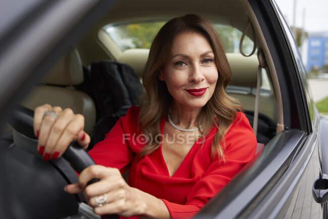 Портрет усміхненої дорослої жінки в машині. — стокове фото