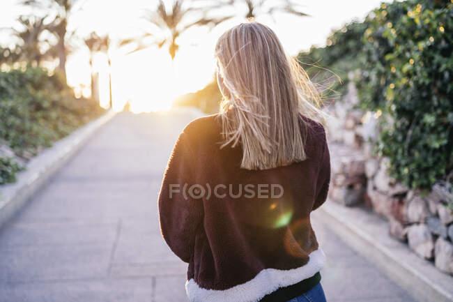 Mujer joven con chaqueta de piel caminando por la calle al atardecer - foto de stock