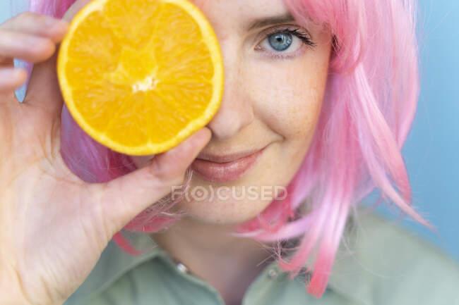 Mujer joven con peluca rosa cubriendo su ojo con una naranja - foto de stock