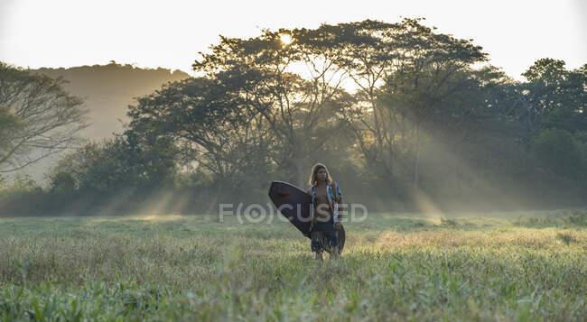 Joven surfista camino a la playa al amanecer, Costa Rica - foto de stock