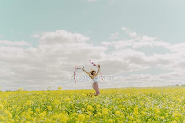 Fröhliche junge Frau bewegt sich im Frühling mit bunten Bändern auf einer Blumenwiese — Stockfoto