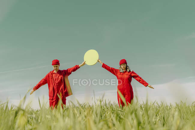 Pareja joven vistiendo monos rojos y sombreros de pie en un campo sosteniendo círculo verde - foto de stock