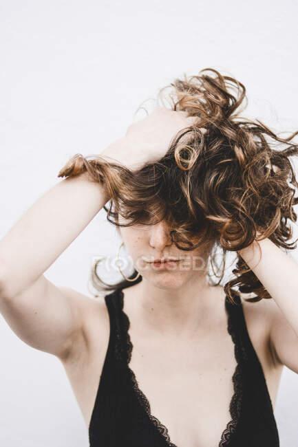 Ritratto di giovane donna con le mani nei capelli — Foto stock