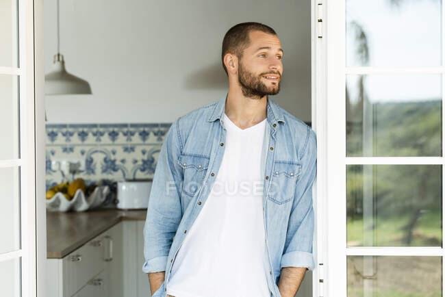 Jovem confiante de pé na porta em casa e olhando para fora — Fotografia de Stock