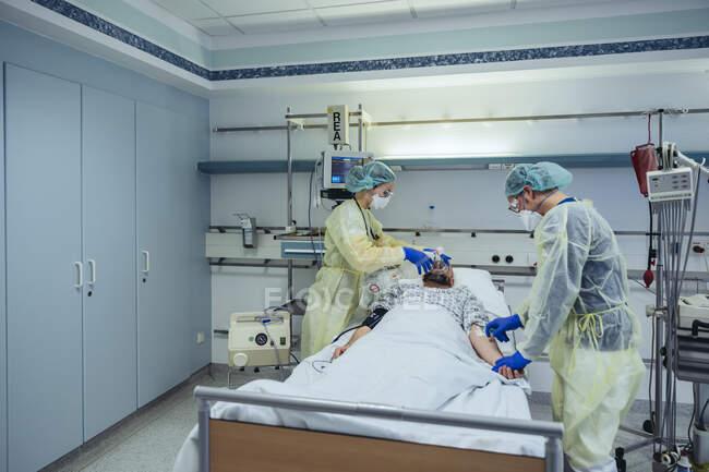 Médicos que cuidam do paciente em uma unidade de emergência de um hospital mudando a respiração de máscara de oxigênio para máscara de válvula de bolsa — Fotografia de Stock