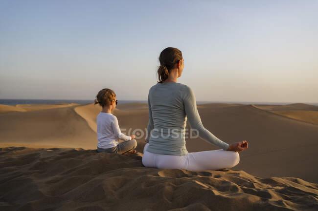 Мать и дочь практикуют йогу в песчаных дюнах на закате, Гран-Канария, Испания — стоковое фото