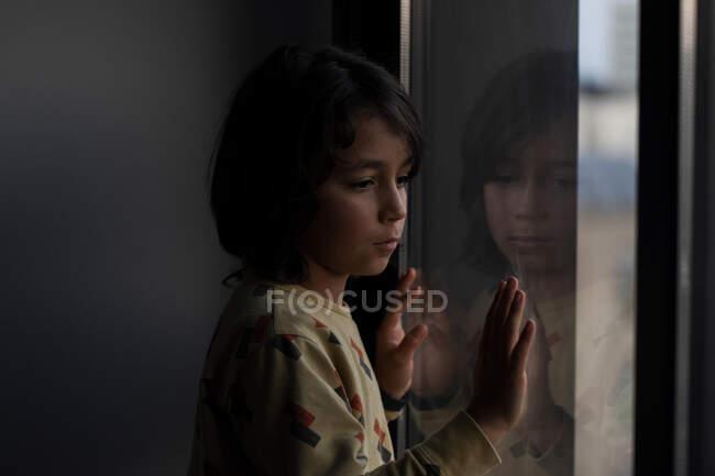 Junge schaut zu Hause aus dem Fenster — Stockfoto
