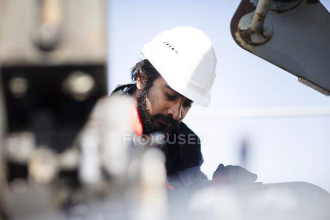 Retrato del técnico con casco y barba trabajando - foto de stock
