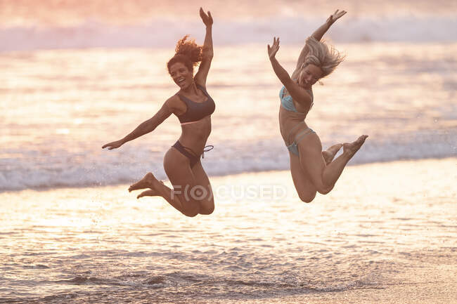 Two carefree women jumping on the beach, Costa Rica — Stock Photo