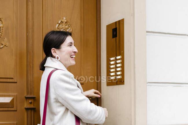 Mujer sonriente abriendo la puerta - foto de stock