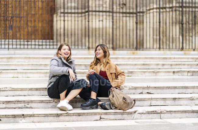 Dos jóvenes felices sentadas en las escaleras de la ciudad - foto de stock