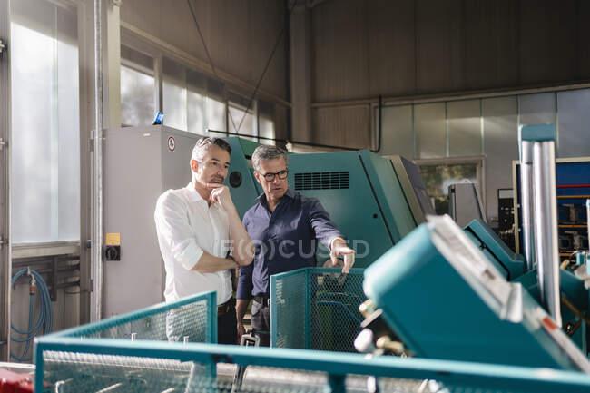 Бізнесмени на фабриці, зустріч, обговорення рішень — стокове фото