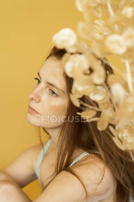 Portrait of pensive redheaded woman against yellow background — Stock Photo