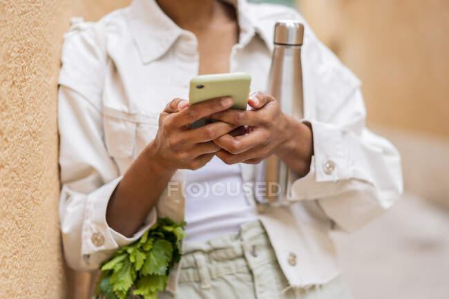 Donna appoggiata a un muro con thermos fiaschetta e generi alimentari utilizzando smartphone — Foto stock