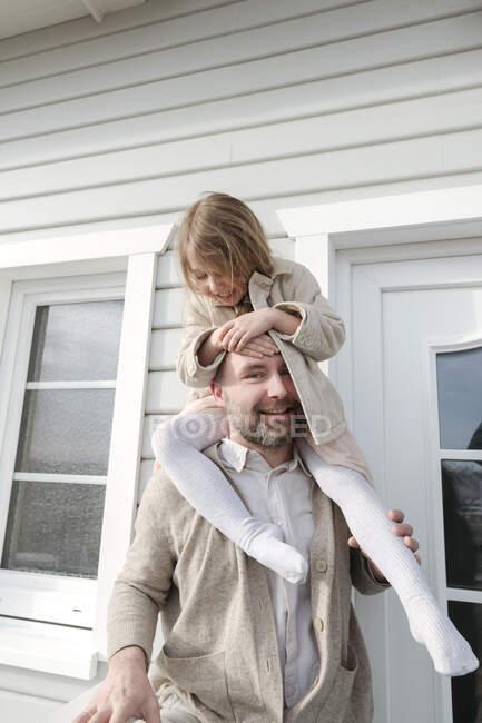 Портрет батька з щасливою дочкою на плечах перед їхнім домом. — стокове фото