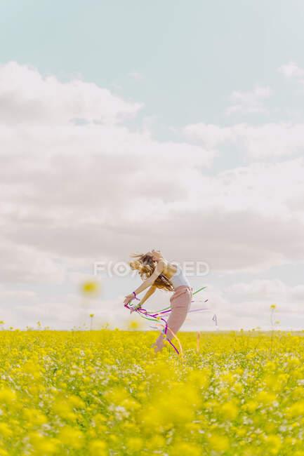 Mujer joven feliz moviéndose con cintas de colores en un prado de flores en primavera - foto de stock
