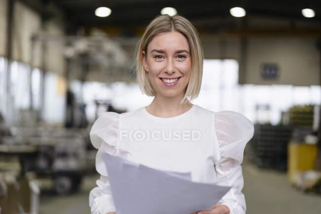 Портрет усміхненої молодої жінки, що тримає документи на фабриці. — стокове фото