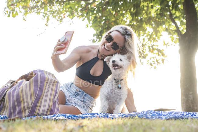 Hermosa mujer tomando una selfie con su perro en la playa, Costa Rica - foto de stock
