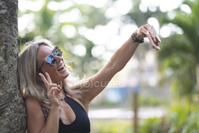 Hermosa mujer apoyada en tronco de árbol usando smartphone, Costa Rica - foto de stock