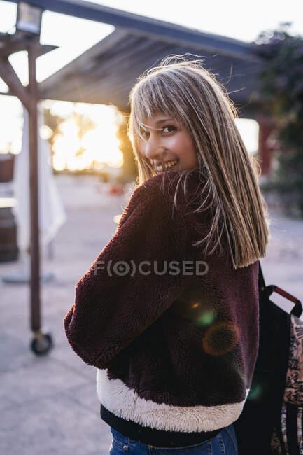 Mujer joven con chaqueta de piel en la ciudad al atardecer - foto de stock