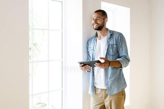 Joven hombre sonriente en casa sosteniendo la tableta de pie en la ventana y mirando al exterior - foto de stock