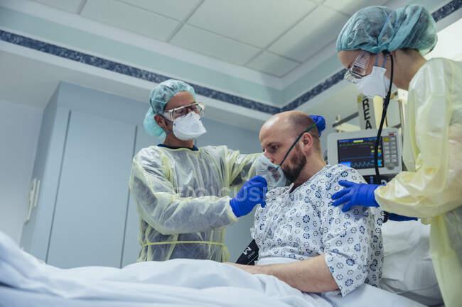 Врачи, проводящие искусственное дыхание пациента в отделении неотложной помощи больницы — стоковое фото