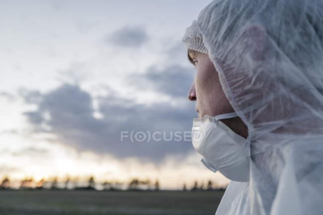 Retrato del hombre con traje protector y máscara mirando el atardecer - foto de stock