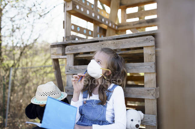 Chica con máscara protectora sentada en el jardín en la casa del árbol y mirando hacia arriba durante la cuarentena corona - foto de stock