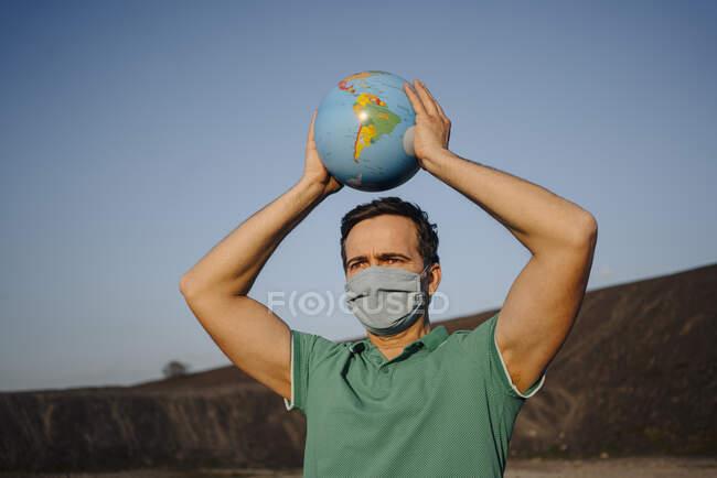 Зрілий чоловік з маскою, що тримає глобус на занедбаному кінці. — стокове фото