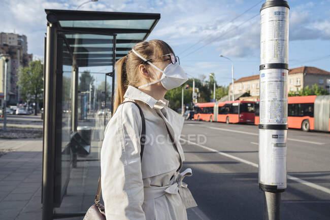 Mulher usando máscara facial verificando cronograma de transporte público na cidade — Fotografia de Stock