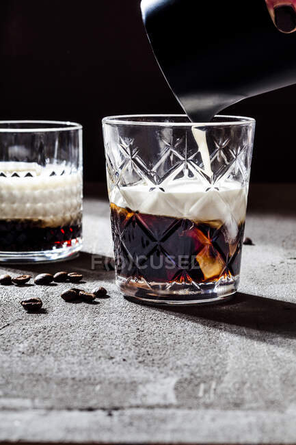Пошкоджена рука жінки, яка поливає вершки в білому російському коктейлі на бетонному столі. — стокове фото