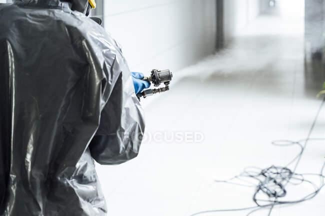 Очищення персоналу, що дезінфікує лікарню від інфекційного вірусу, носить захисний одяг. — стокове фото