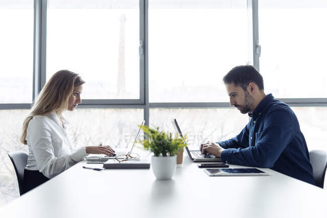 Бізнесмен і жінка сидять за столом, користуються ноутбуками, серйозно дивляться. — стокове фото