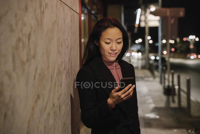 Mujer joven usando smartphone en la ciudad por la noche, Frankfurt, Alemania - foto de stock