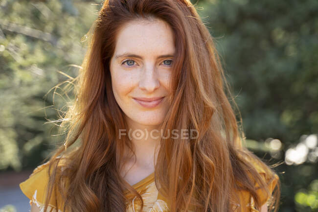 Portrait of smiling redheaded woman outdoors — Stock Photo
