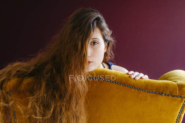Close-up retrato de jovem mulher com cabelos castanhos longos encostados na cadeira dourada contra fundo colorido — Fotografia de Stock