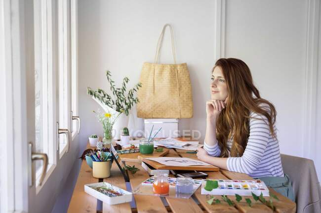 Thoughtful young woman looking away while painting on table at home — Stock Photo