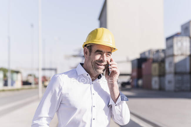 Portrait of smiling businessman on the phone at industrial site — Stock Photo