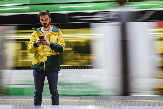 Homem usando telefone celular na estação de metrô — Fotografia de Stock