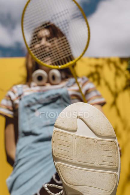 Mujer joven sosteniendo raqueta de bádminton con suela de zapato en primer plano durante el día soleado - foto de stock