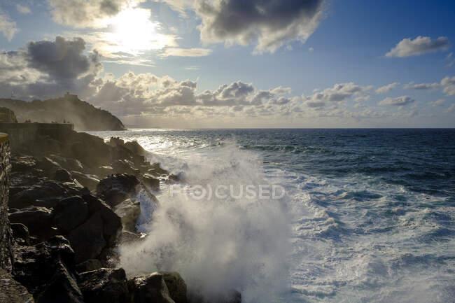 Spagna, Gipuzkoa, San Sebastian, Onde che schizzano contro la costa rocciosa — Foto stock