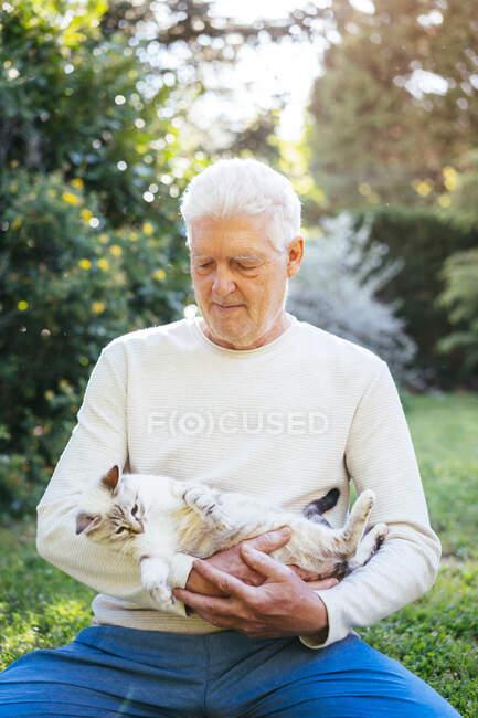 Hombre mayor abrazándose con su gato en el jardín - foto de stock