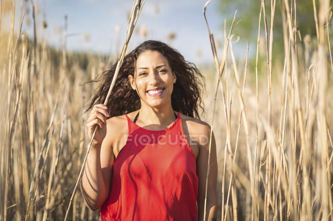 Portrait de jeune femme heureuse parmi roseau — Photo de stock