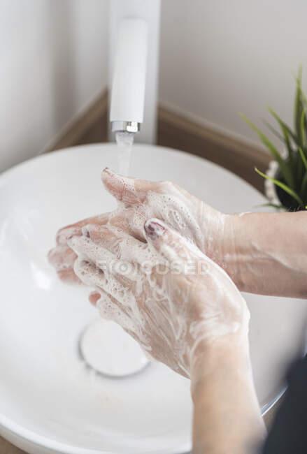 Primer plano de la mujer lavándose la mano con jabón - foto de stock