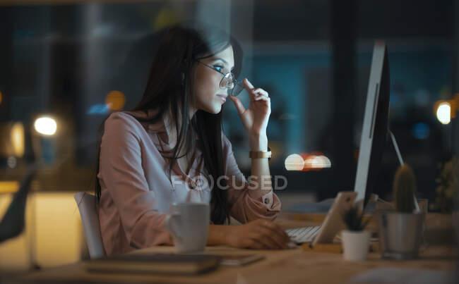 Молода жінка з окулярами в офісі. — стокове фото
