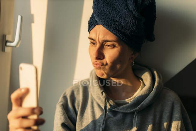Mujer joven mirando el teléfono celular en casa haciendo pucheros - foto de stock