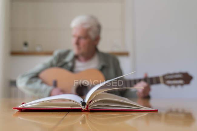 Крупный план дневника и ручки на столе со старшим мужчиной, практикующим гитару, сидя дома — стоковое фото